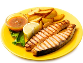 Salmon on grill with sauce and french fries